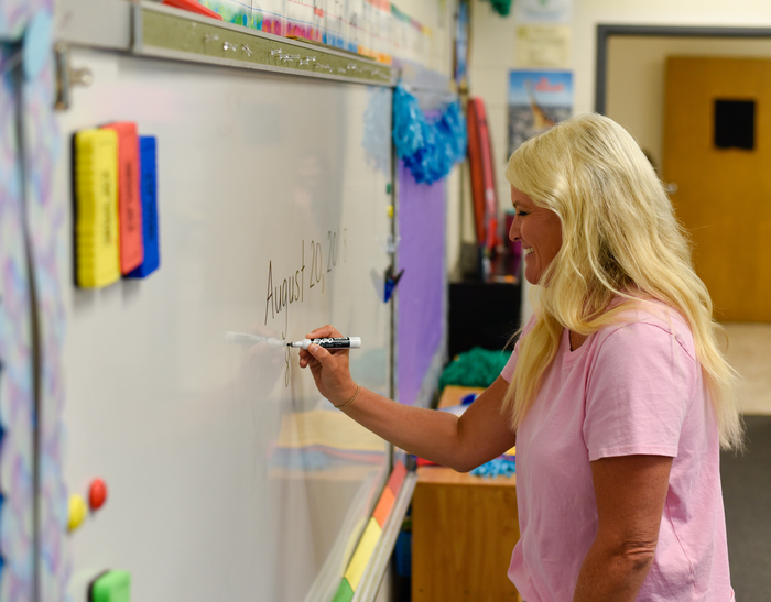 Julie Brewster, a first grade teacher at Iva Elementary, writes the date for the first day of school on the board.