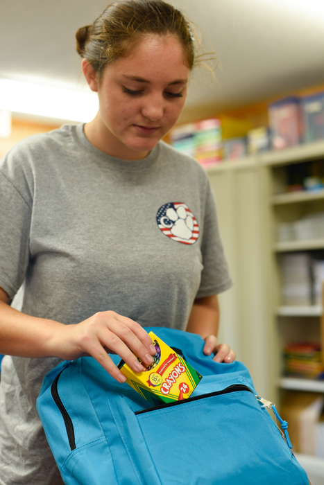 Haley Pepper packs a book bag with a box of Crayola Crayons.