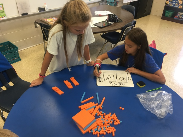 5th graders using concrete models to review multiplication.