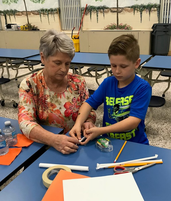Families work together to construct rockets.