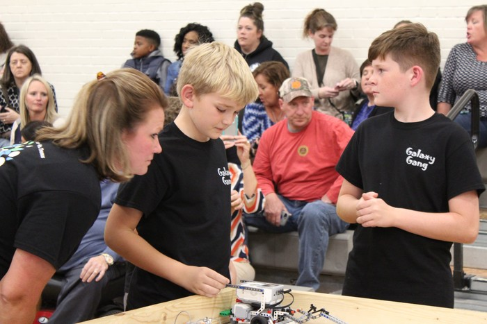 Students adjust their robot in the District competition.