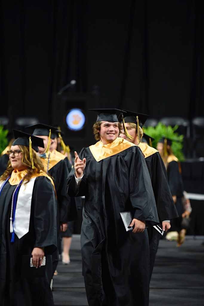 Student waves to his family after receiving his diploma.